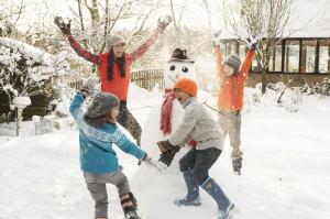 Дети играют в снежки на заснеженном газоне