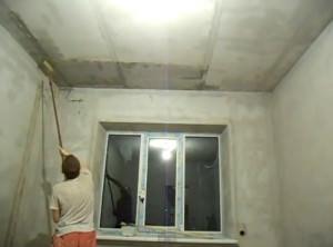 Мужчина грунтует потолок валиком на длинной ручке