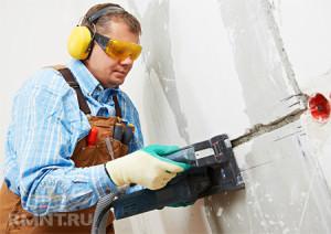 Мужчина в защитной одежде штробит стену